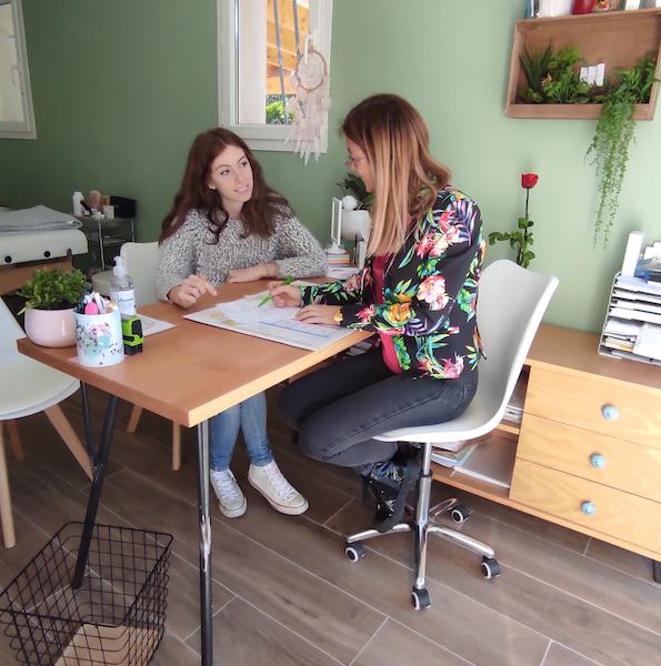 le naturopathe fait un bilan de santé à sa patiente assise à son bureau